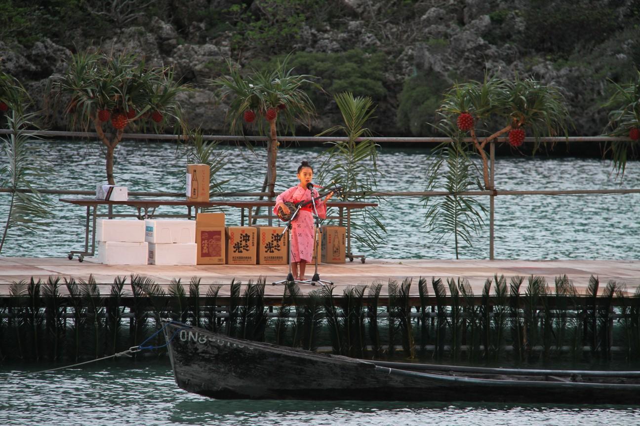 海上ステージの前にはサバニが浮かべられています。子どもたちも堂々と「なりやまあやぐ」を唄いました。